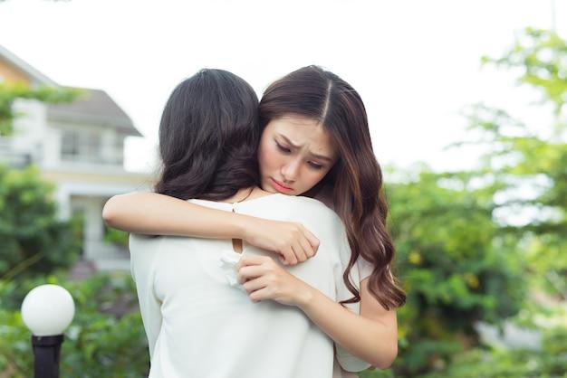 Vriendschap hulp ondersteuning. gedeprimeerde aziatische vrouw die haar vriend omhelst.