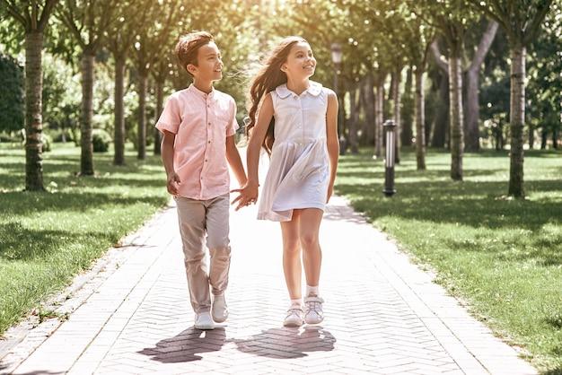 Vriendschap kleine jongen en meisje lopen op de weg in het park