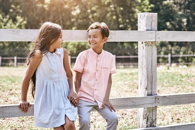 Vriendschap kleine jongen en meisje lopen samen buiten leanin