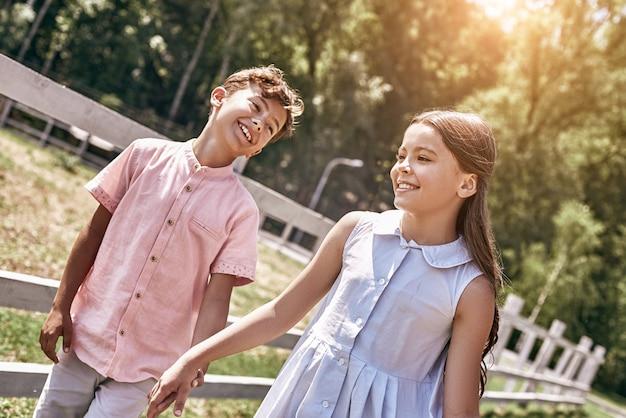 Vriendschap kleine jongen en meisje lopen samen buitenshuis holdin