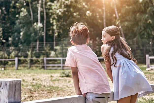 Vriendschap kleine jongen en meisje samen buiten leunend op fen