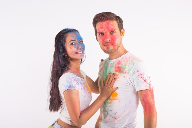 Vriendschap, liefde, festival van holi, mensen concept - jong koppel spelen met kleuren op het festival van holi op witte ondergrond