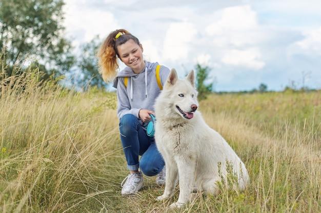 Vriendschap meisjes en honden, tiener en huisdier husky wandelen buiten