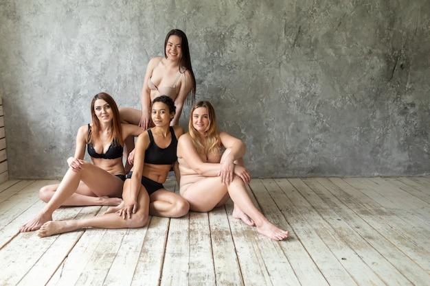 Vriendschap, schoonheid, positief lichaam en mensenconcept - groep gelukkige vrouwen verschillend in ondergoed over grijze achtergrond. hoge kwaliteit foto