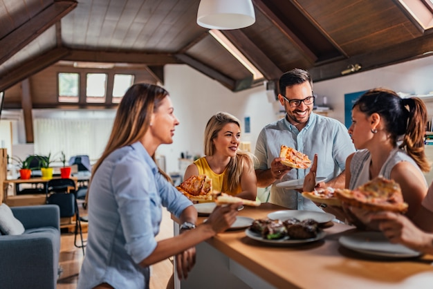 Vriendschappelijk commercieel team die pizza samen in het coworking van bureau eten.