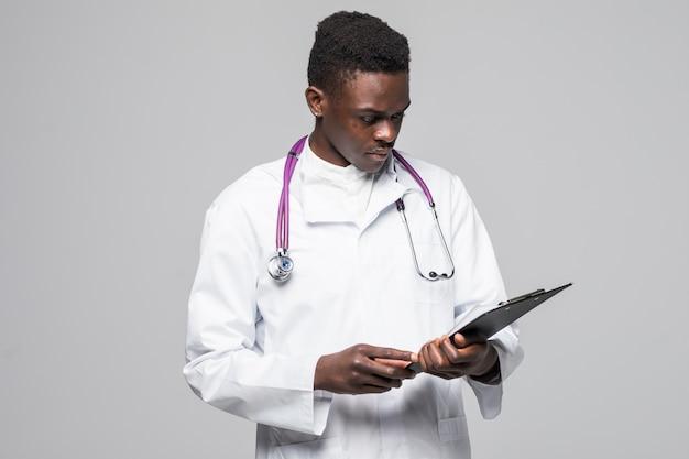 Vriendschappelijke afro-amerikaanse arts die een klembord houdt en bij de camera glimlacht die op grijze achtergrond wordt geïsoleerd