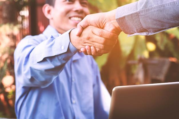 Vriendschappelijke bedrijfsmens die een handdruk en het glimlachen geeft