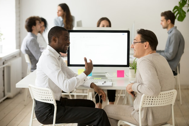 Vriendschappelijke glimlachende diverse mannelijke collega's die prettig gesprek hebben op het werk