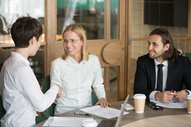 Vriendschappelijke onderneemsters die handen schudden op groepskantoorvergadering met zakenman