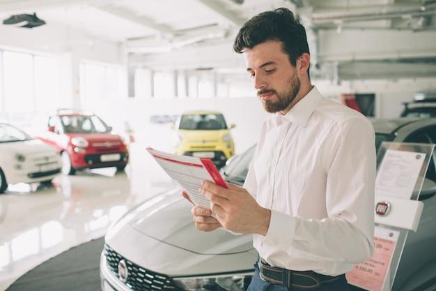 Vriendschappelijke voertuigverkoper die nieuwe auto's voorstellen bij toonzaal.