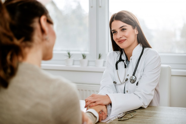 Vriendschappelijke vrouwelijke arts die de hand van de vrouwelijke patiënt voor aanmoediging en empathie houdt.