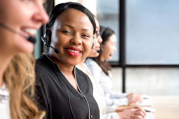 Vriendschappelijke zwarte die microfoonhoofdtelefoon draagt die in call centre werkt