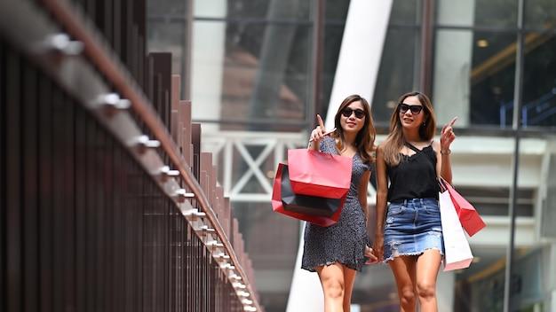 Vriendschappenwijfje die met het winkelen zak lopen, het winkelen concept.