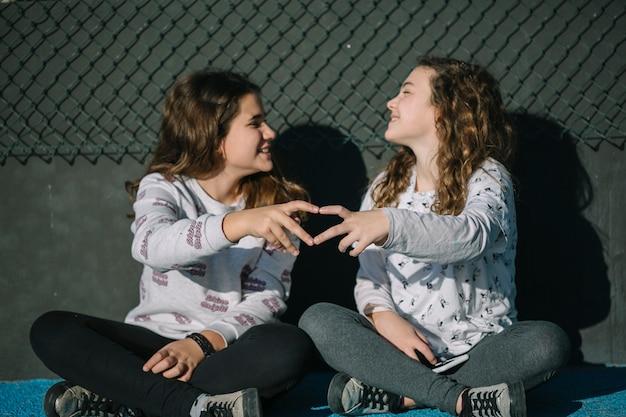 Vriendschapsconcept met meisjes die op dak zitten