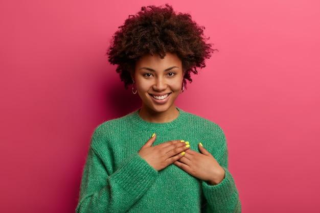 Vrij aangeraakte vrouw drukt handpalmen tegen het hart, drukt positieve gevoelens uit, voelt zich aangeraakt om hulp te krijgen, maakt dankbaarheidsgebaar, draagt warme groene trui, glimlacht oprecht, geïsoleerd op roze muur