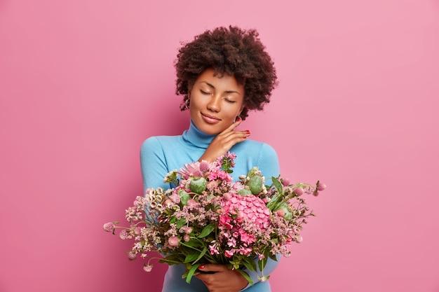Vrij aanhankelijke vrouw raakt zachtjes kaaklijn stands met gesloten ogen houdt grote bos bloemen
