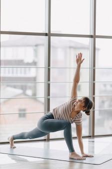 Vrij aantrekkelijk meisje dat yoga in een heldere ruimte doet