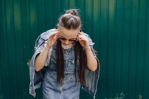 Vrij aantrekkelijk meisje in denim kleding in glazen op een eenvoudige donkergroene achtergrond met lege ruimte voor tekst