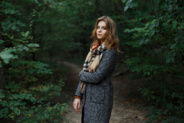 Vrij aantrekkelijke europese jonge vrouw in een modieuze geruite sjaal in een chique grijze jas loopt in het bos in de buurt van groene struiken