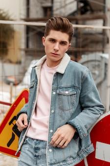 Vrij aantrekkelijke jonge man in roze glamoureuze t-shirt in stijlvol spijkerjasje staat in de buurt van bouwplaats en metalen verkeersborden. modieus kerelmodel in vrijetijdsjeanskleding voor jongeren loopt buiten.
