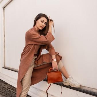 Vrij aantrekkelijke jonge vrouw in mode mooie elegante jas in beige broek in stijlvolle sneakers met lederen handtas poseren in de buurt van muur in de stad. het leuke modieuze meisje maakt haar recht. lieve vrouw