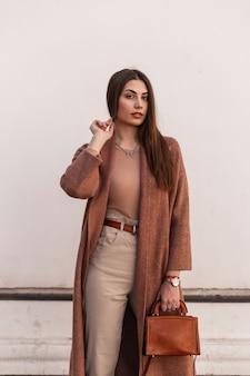 Vrij aantrekkelijke jonge vrouw mannequin in elegante bruine kleding met lederen mode handtas poseren in de buurt van vintage wit gebouw op straat. mooi meisje in casual outfit buitenshuis. schoonheidsdame.