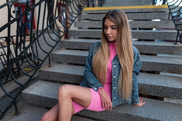 Vrij aantrekkelijke jonge vrouw met lang haar in een trendy zomer roze sportief pak in een glamoureuze stijlvolle denim jasje rust zittend op een vintage trap in de stad. vrij modern stedelijk meisje.