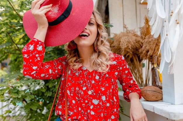 Vrij aantrekkelijke stijlvolle blonde lachende vrouw in rode strooien hoed en blouse zomer mode outfit café