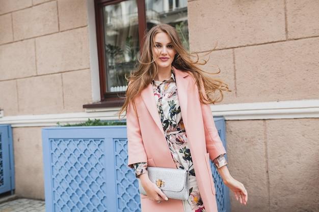 Vrij aantrekkelijke stijlvolle lachende vrouw lopen stad straat in roze jas lente modetrend draaien