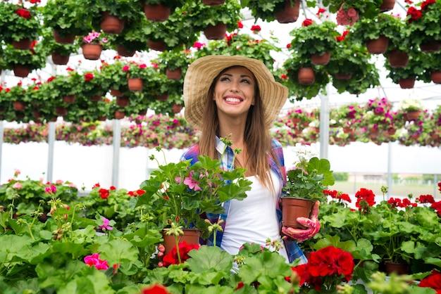 Vrij aantrekkelijke vrouwenbloemist die in het tuincentrum van de serre werkt die ingemaakte bloemen voor verkoop schikt