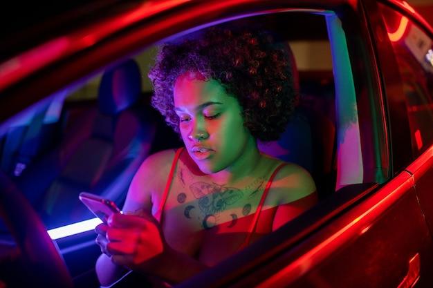 Vrij afrikaans meisje dat in smartphone scrolt terwijl ze gaat rijden