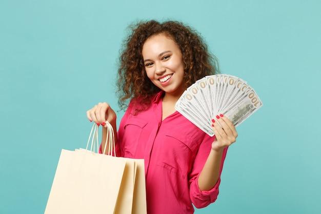 Vrij afrikaans meisje houdt pakkettas vast met aankopen na het winkelen, fan van geld in dollarbankbiljetten, contant geld geïsoleerd op blauwe turkooizen achtergrond. mensen levensstijl concept. bespotten kopie ruimte.