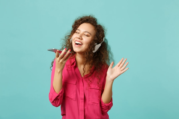 Vrij afrikaans meisje in casual kleding houdt mobiele telefoon vast, luistert muziek met koptelefoon geïsoleerd op blauwe turkooizen achtergrond in studio. mensen oprechte emoties levensstijl concept. bespotten kopie ruimte.