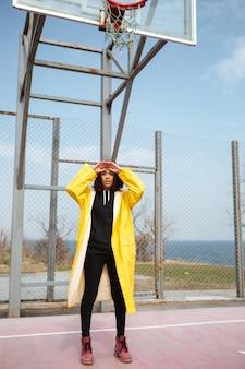 Vrij afrikaanse krullende jonge vrouw die gele laag draagt