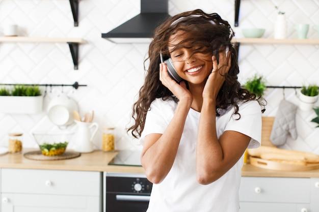 Vrij afrikaanse vrouw wervelt haar hoofd en luistert naar muziek via een koptelefoon in de keuken