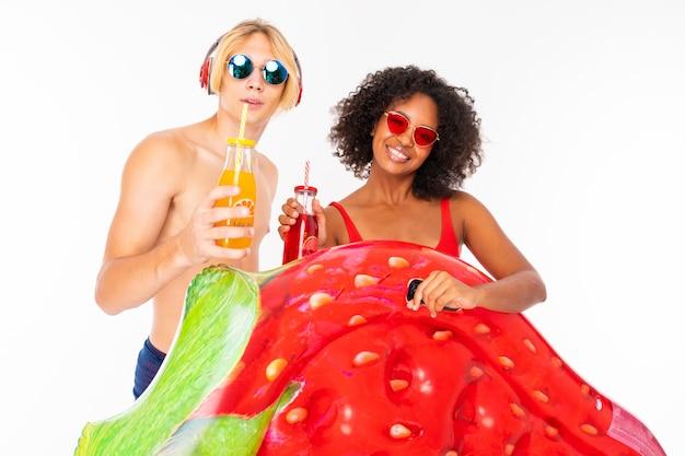 Vrij afrikaanse vrouwelijke en kaukasische blonde man staat in zwembroek met rubberen strandmatrassen, drinkt sap en glimlacht geïsoleerd op een witte achtergrond