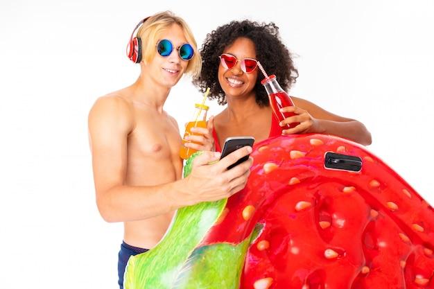 Vrij afrikaanse vrouwelijke en kaukasische blonde man staat in zwembroek met rubberen strandmatrassen, drinkt sap en luister naar muziek geïsoleerd op een witte achtergrond