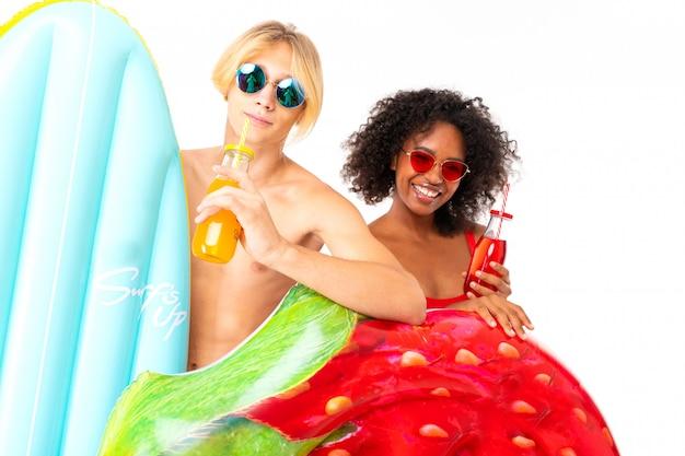 Vrij afrikaanse vrouwelijke en kaukasische blonde man staat in zwembroek met rubberen strandmatrassen en glimlacht geïsoleerd op een witte achtergrond