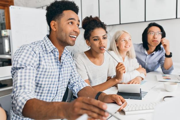 Vrij afrikaanse vrouwelijke student die potlood bijt terwijl hij aan iets denkt. indoor portret van tevreden zwarte kantoormedewerker in geruit blauw shirt aan de tafel zitten met collega's.