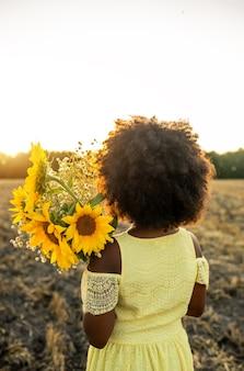 Vrij afro-amerikaans meisje in een zonnebloemenveld met plezier