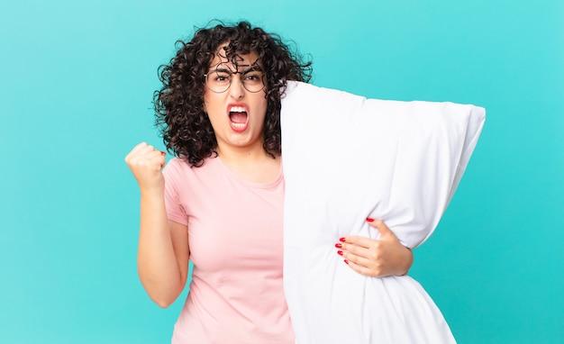 Vrij arabische vrouw die agressief schreeuwt met een boze uitdrukking. een pyjama dragen en een kussen vasthouden
