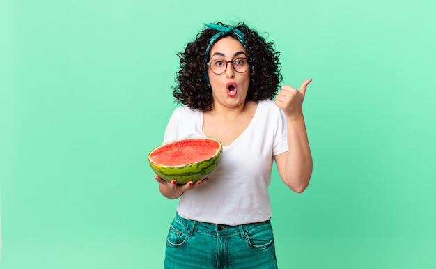 Vrij arabische vrouw die verbaasd in ongeloof kijkt en een watermeloen vasthoudt. zomer concept