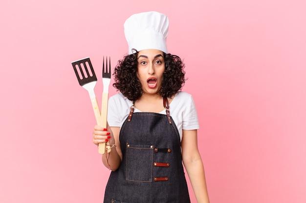 Vrij arabische vrouw die zeer geschokt of verrast kijkt. barbecue chef-kok concept