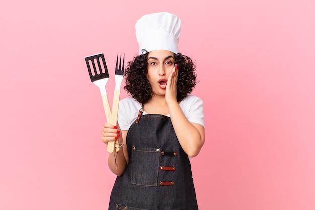 Vrij arabische vrouw die zich geschokt en bang voelt. barbecue chef-kok concept