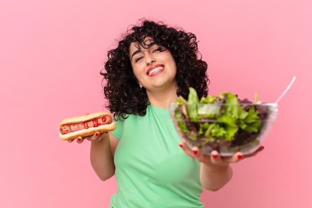 Vrij arabische vrouw met een salade en een hotdog. dieet concept