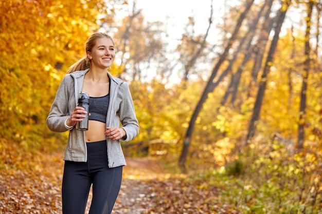 Vrij atletische vrouw draait op zonnige herfstdag, geniet van het joggen. aport en welzijnsconcept