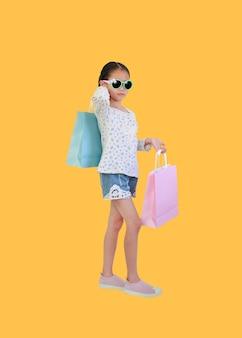 Vrij aziatisch klein kindmeisje die zonnebril dragen die boodschappentassen op geel houden