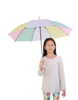 Vrij aziatisch klein kindmeisje met veelkleurige paraplu op witte geïsoleerde achtergrond met uitknippad. kid bedrijf kleurrijke paraplu.