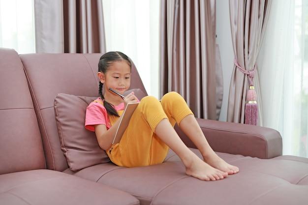 Vrij aziatisch klein meisje dat op een boek schrijft dat thuis op de bank ligt