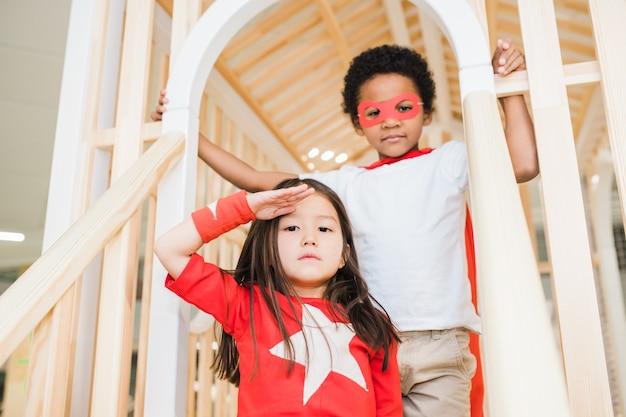 Vrij aziatisch meisje houdt de hand bij haar voorhoofd terwijl ze dicht bij de kleine afrikaanse jongen staat tijdens het spelen in het recreatiecentrum